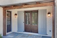 The side porch with cedar beams, metal roof, stained doors, and bluestone floors.