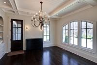 Another view of the dining room with its dark oak floors, arched windows, and custom woodwork.  The chandelier was sourced by the homeowner and fits the space perfectly.