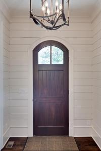 Interior view of the front door showing the paneled wood walls and trim of the entry hall.