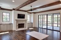 Great room with stained cedar beams, oak flooring, custom stone fireplace surround, and large open sliders to the screened back porch.