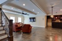 Terrace level entertaining area with stained concrete floors and full bar.