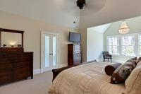 Another view of the master bedroom showing the frosted glass French doors leading to the bathroom and closet area.