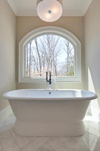 Free standing master bath tub with arched window overlooking the rear of the property.