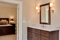 Master bath vanity stained dark brown with matching mirror frame and chrome sconce lights.