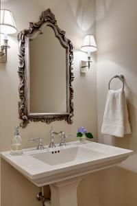 New powder room with pedestal style vanity and custom sconce lights.