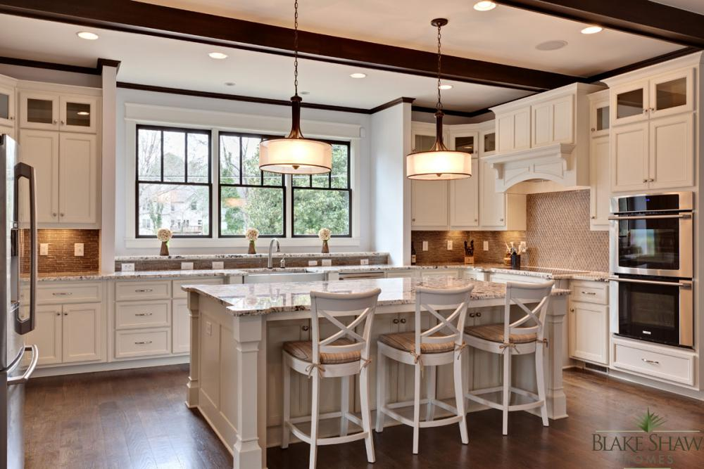 A View Of The Kitchen With Custom Cabinetry, Granite Counters, Stainless  Steel Appliances, And Stained Beam Detail.